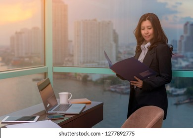 Asian woman holding folder of documents and standing in front of windows in an office building overlooking the city and river.
