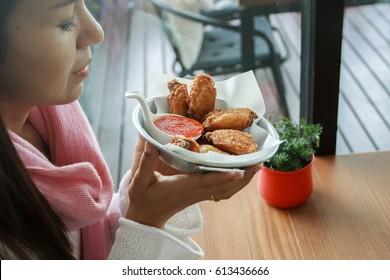 Asian woman holding fried chicken in dish with sauce