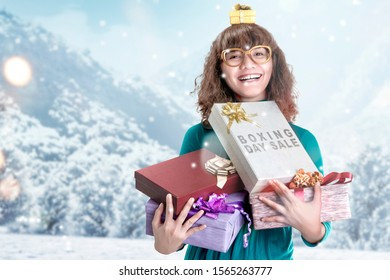 Asian woman holding gift box with Boxing Day Sale text with snowy hill background
