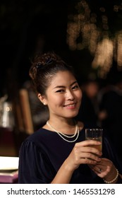 The Asian woman holding glasses in the night party.
