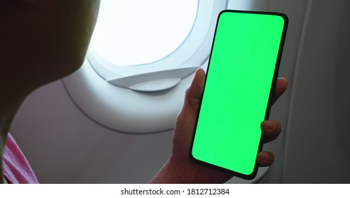 asian woman holding green screen smart phone in airplane cabin
