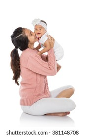 Asian woman holding her baby girl sitting on a floor isolated over white background