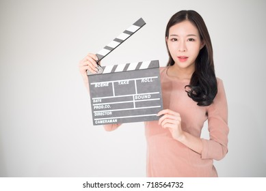 Asian woman holding movie clapper board isolated on white background. Cinematography, communication arts, casting, audition, movie production concept. Movie clapper is the movie shooting equipment.