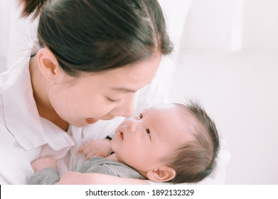 Asian woman holding a newborn baby in her arms at home.Mother day and newborn baby infant health care concept.