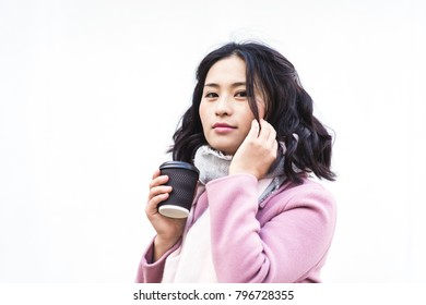 Asian woman holding paper cup of hot drink