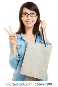 Asian woman holding shopping bag with victory sign
