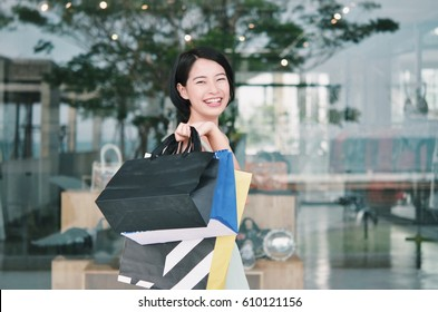 Asian woman holding shopping bag in her hand .