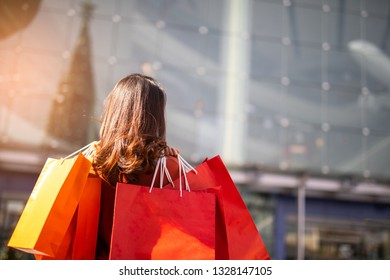 Asian Woman holding shopping bags in the shopping mall .