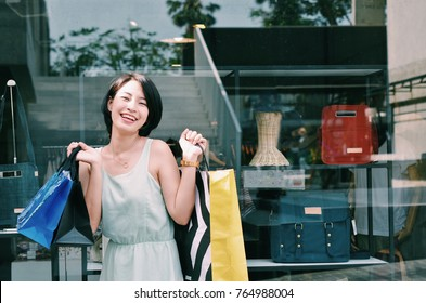 Asian woman holding shopping at outlet mall.
