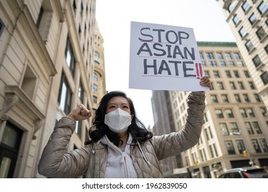 Asian woman holding Stop Asian Hate sign protesting on a street in New York City