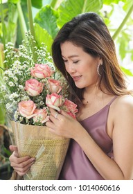 Asian woman holding white, pink roses bouquet in her arm, feeling happy and appreciate flower gif from her lover on Valentine's day