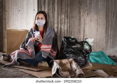 Asian woman homeless wearing hygiene face mask for protective infection and pandemic of coronavirus or covid19. Female beggar wearing sweater and blanket sitting hold bowl for help on walkway street