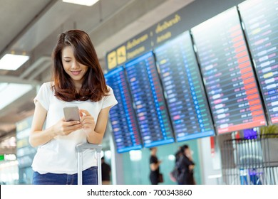 Asian woman information board at airport for buy ticket flight travel vacation in holiday checking online by smartphone