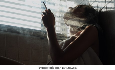 Asian woman inhaling and cigarette vaping. Female secretly smoking in bathroom at home. Concept of quit smoking and anti cigarette.