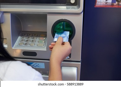 Asian woman inserting card to ATM Machine to withdraw cash. Financial transaction concept.