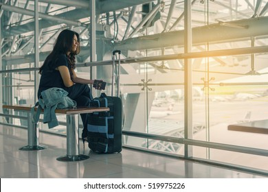 Asian woman at international airport, holding passport, luggage and waiting for her flight and background blur airplane, view from airport terminal. (vintage color tone, lens blur effect)