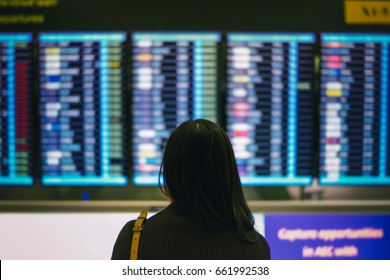 Asian woman in international airport looking at the flight information board, Travel concept