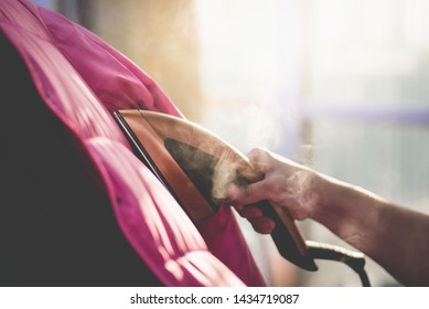 Asian woman Woman ironing down jacket with garment steamer