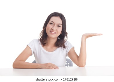 Asian woman isolated on white background. white t-shirt, sit on chair with table, hand upward, looking to camera