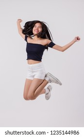 asian woman jumping. studio isolated portrait of happy, smiling, excited woman jumping, leaping, hoppint with joy. young adult asian woman model