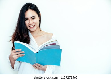 Asian woman just wake up in the morning and relaxed. She open the window to receive the light of the morning sun. She reading a blue book.