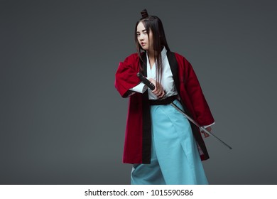 asian woman in kimono holding katana sword and looking at camera isolated on grey