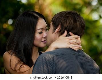 asian woman kissing caucasian man