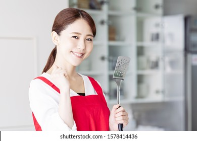 Asian woman in kitchen. Cooking. Restaurant.