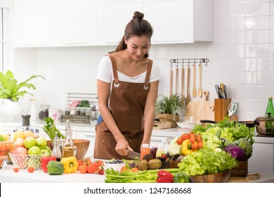 Asian woman in a kitchen cutting vegetables and preparing healthy meal and salad