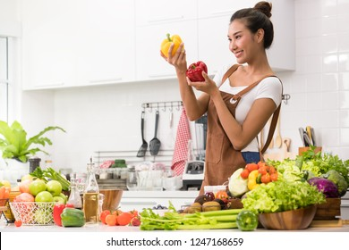 Asian woman in a kitchen preparing fruits and vegetables for healthy meal and salad