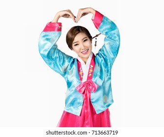 Asian woman in Korean traditional dress making heart shape with arms on white background isolated with clipping path