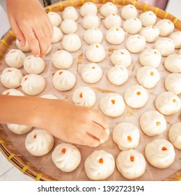 Asian woman is laying Baozi or Bun on bamboo basket in a typical Chinese home, close shot of woman hands is laying Baozi. Homemade food. Food culture.