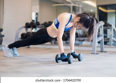 Asian woman lifting dumbbells in fitness room. Young woman lifting dumbbells in the gym.
