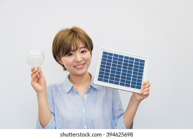 asian woman with light bulb and solar panel
