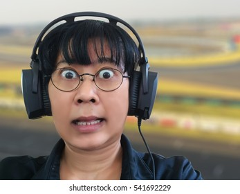 An Asian woman listening to the excited program broadcast by headphone on blur racetrack background