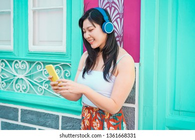 Asian woman listening music with smartphone app outdoor - Happy chinese girl having fun with new trends technology - Fashion, tech and millennial generation activity - Focus on face