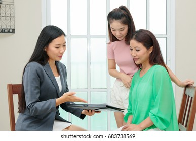Asian woman listens to a saleswoman or insurance consultant sitting at table in home
