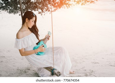 Asian woman lonely playing ukulele sitting on swing at beach with acoustic classic song wearing white dress solitude alone,sad love on summer season