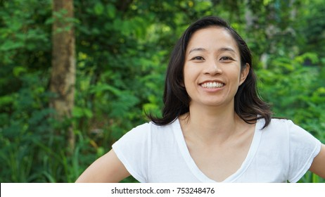 Asian woman long hair facial epression green nature background