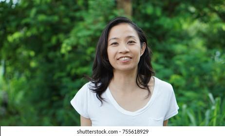 Asian woman long hair facial epression green nature background