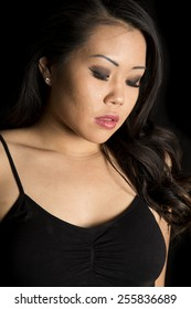 an Asian woman looking down on a black background.