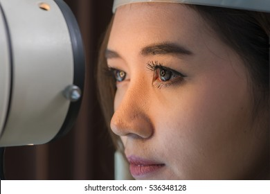 Asian woman looking at eye test machine in ophthalmologist. ophthalmologist. medical, health, (Advertise, Ophthalmology concept)