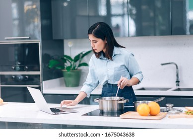 Asian Woman Looking Food Recipes on Laptop and Cooking New Menu for Dinner - Shutterstock ID 1675043638