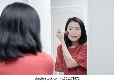 Asian woman looking in the mirror and holding a blush for blush cheek makeup.