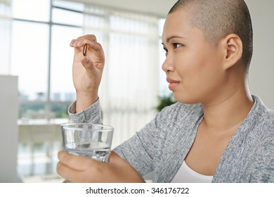 Asian woman looking at pill in her hand