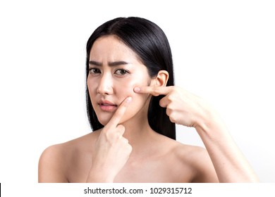 Asian woman looking at pimple on face. Young Woman try to remove her pimple. Woman skin care concept. Isolated on white background.