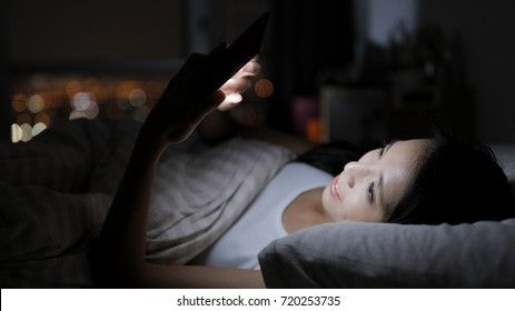 Asian Woman looking at smart phone and lying on bed