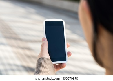 Asian woman looking at the smartphone