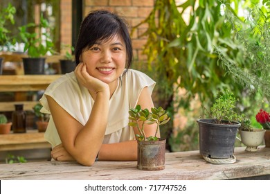 THe Asian woman is looking to some small plant in the black pot in the outdoor coffee shop with the flare from the picture edge.
