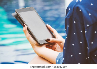asian woman looking to tablet for shopping online and nature background. subject is blurred